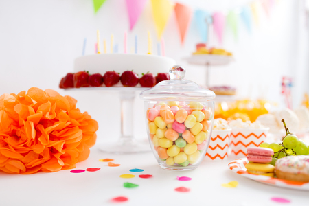 food, confectionery and sweets concept - glass jar with colorful candy drops at birthday party Stock Photo