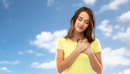 appreciation, valentines day and sincere emotions concept - thankful young woman or teenage girl with closed eyes in yellow t-shirt holding hands on chest or heart over blue sky and clouds background