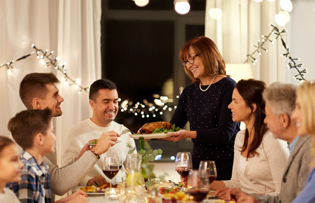 celebration, holidays and people concept - happy senior woman offering roast chicken to family having dinner party at home