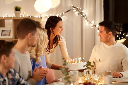 concepto de celebración y personas - familia feliz con pastel con fiesta de cumpleaños en casa