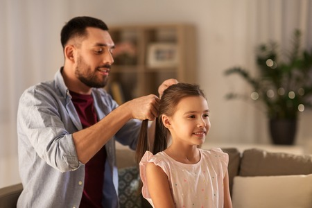 family and people concept - happy father braiding daughter hair at home Stock Photo