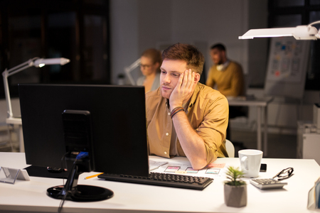 business, overwork, deadline and people concept - tired or bored man working at computer at night office Imagens - 119565219