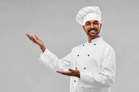 cooking, profession and people concept - happy male indian chef in toque over grey background Foto de archivo