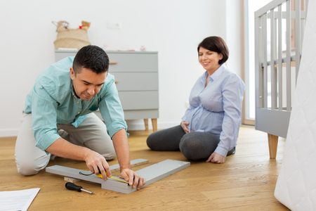 family couple assembling baby bed at home