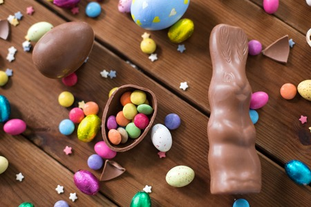 chocolate eggs, easter bunny and candies on wood Фото со стока