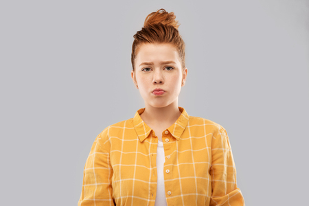 sad red haired teenage girl in shirt pouting Stock Photo