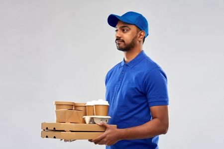 service and people concept - indian delivery man with food and drinks in blue uniform over grey background
