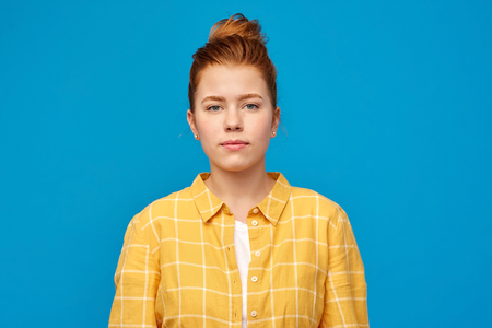 people concept - red haired teenage girl in checkered shirt over bright blue background
