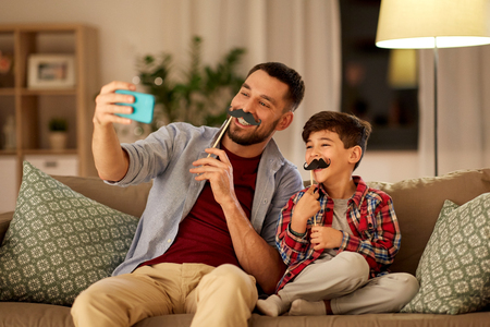 people, family and technology concept - happy father and little son with mustaches party props taking selfie by smartphone sitting on sofa at home in evening Stockfoto