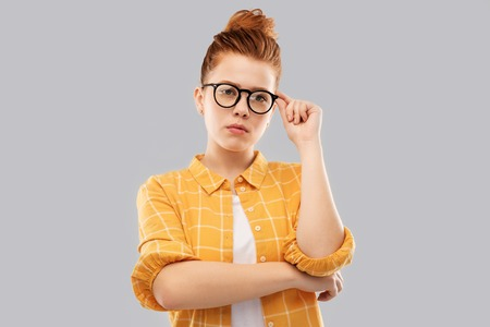 vision, education people concept - red haired teenage student girl in glasses and checkered shirt over grey background Stock Photo