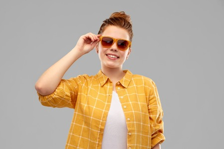 summer, eyewear and people concept - smiling red haired teenage girl in sunglasses and yellow checkered shirt over grey background