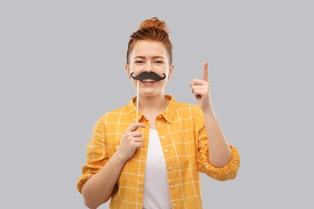 party props, photo booth and people concept - joyful red haired teenage girl in checkered shirt with big black moustaches pointing finger up over grey background