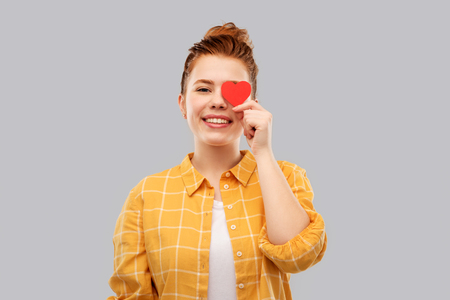love, valentine's day and charity concept - smiling red haired teenage girl in checkered shirt with heart covering one eye over grey background Stock fotó