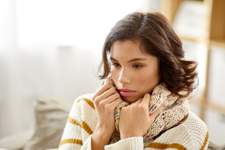 people, health and cold concept - sad sick woman in scarf at home