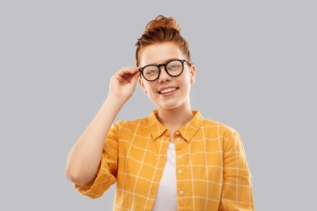 Smiling red haired teenage student girl in glasses