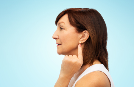 senior woman pointing to her golden earring