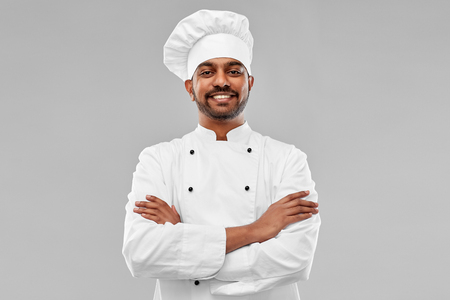 happy male indian chef in toque Stockfoto