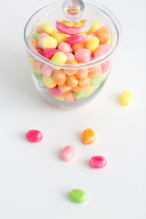 close up of glass jar with colorful candy drops