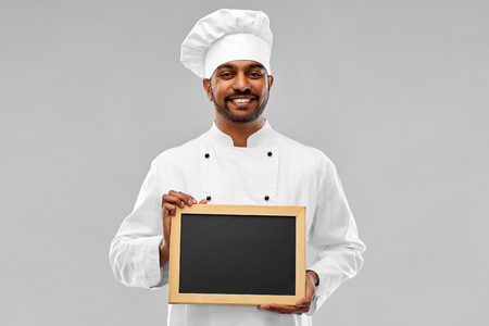happy male indian chef in toque with chalkboard Stock Photo