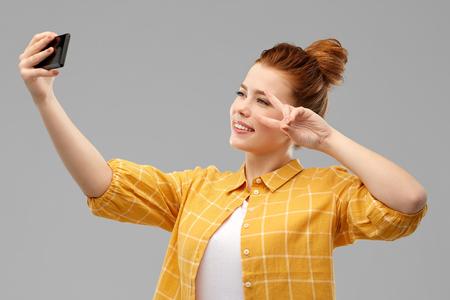 redhead teenage girl taking selfie by smartphone Stock Photo