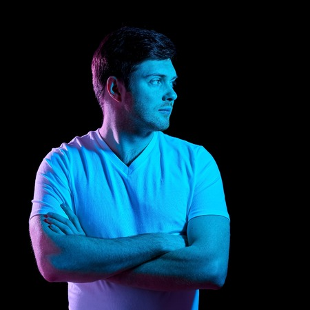 man with crossed arms over neon lights in darkness Stock Photo