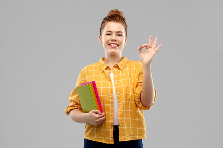 redhead teenage student girl with books showing ok