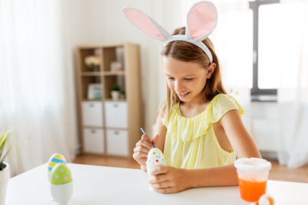 happy girl coloring easter eggs at home Stock Photo