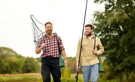 friends with fishing rods and net walking outdoors