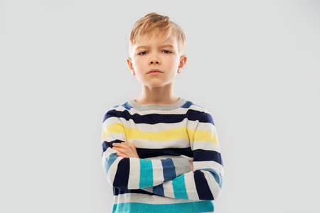 little boy in striped pullover with crossed arms