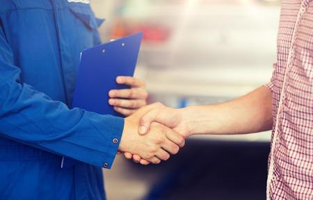 mechanik samochodowy i mężczyzna uścisk dłoni w sklepie samochodowym