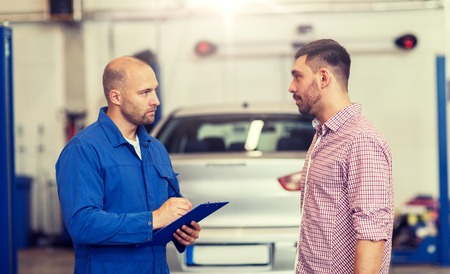 auto mechanic with clipboard and man at car shop 版權商用圖片