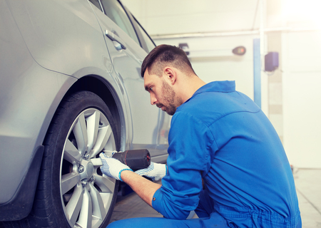 mechanic with screwdriver changing car tire
