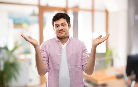young man shrugging over office room