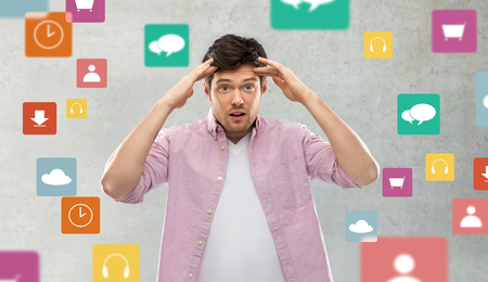 man touching his head over app icons on grey