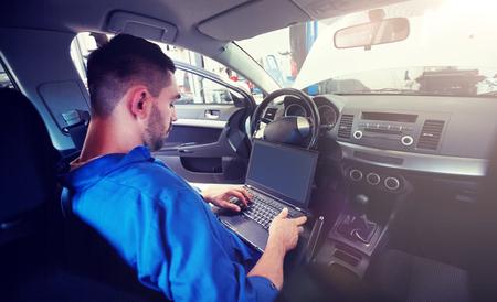 mechanic man with laptop making car diagnostic 版權商用圖片