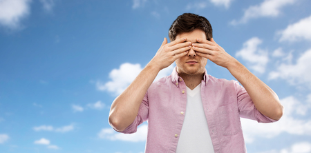 man closing his eyes by hands over blue sky