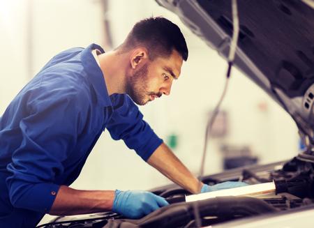mechanic man with lamp repairing car at workshop