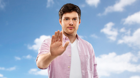 young man showing stop gesture over blue sky