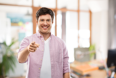 smiling man pointing fingers at you over office
