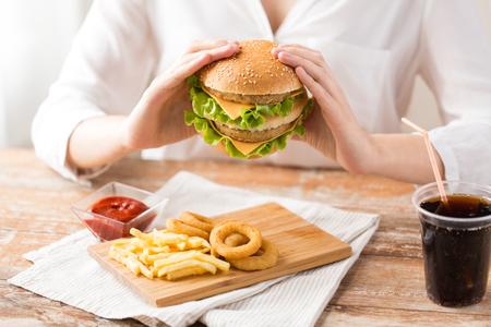 close up of woman eating hamburger at restaurant