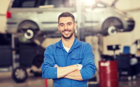 happy auto mechanic man or smith at car workshop Banco de Imagens