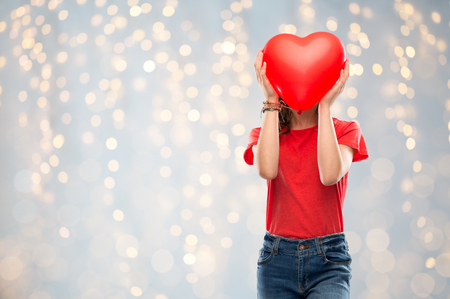 teenage girl with red heart shaped balloon Stock Photo