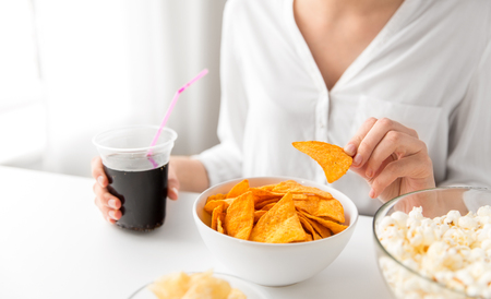 close up of woman eating corn nachos with cola Reklamní fotografie