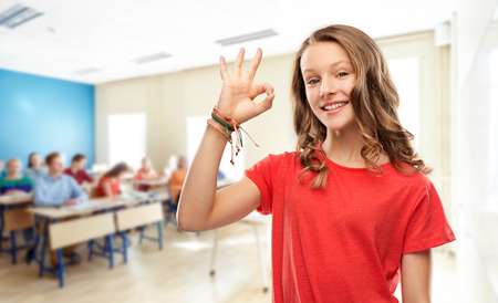 smiling teenage student girl showing ok at school