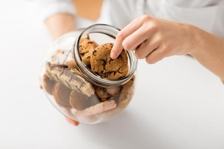 Cerca de mujer tomando galletas de avena de jar