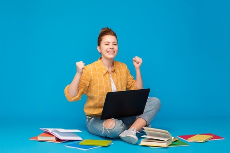 happy student girl with laptop celebrating success
