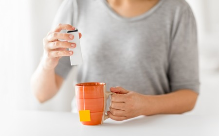 close up of woman adding sweetener to cup of tea