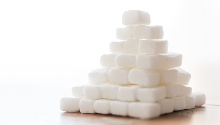 close up of white lump sugar pyramid on table