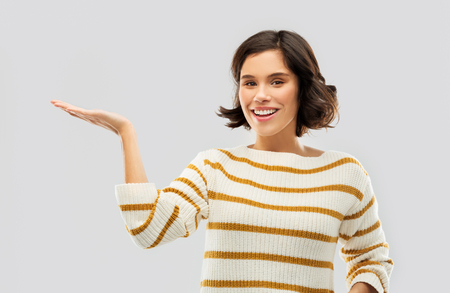 smiling young woman holding empty palm