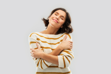 happy woman in striped pullover hugging herself